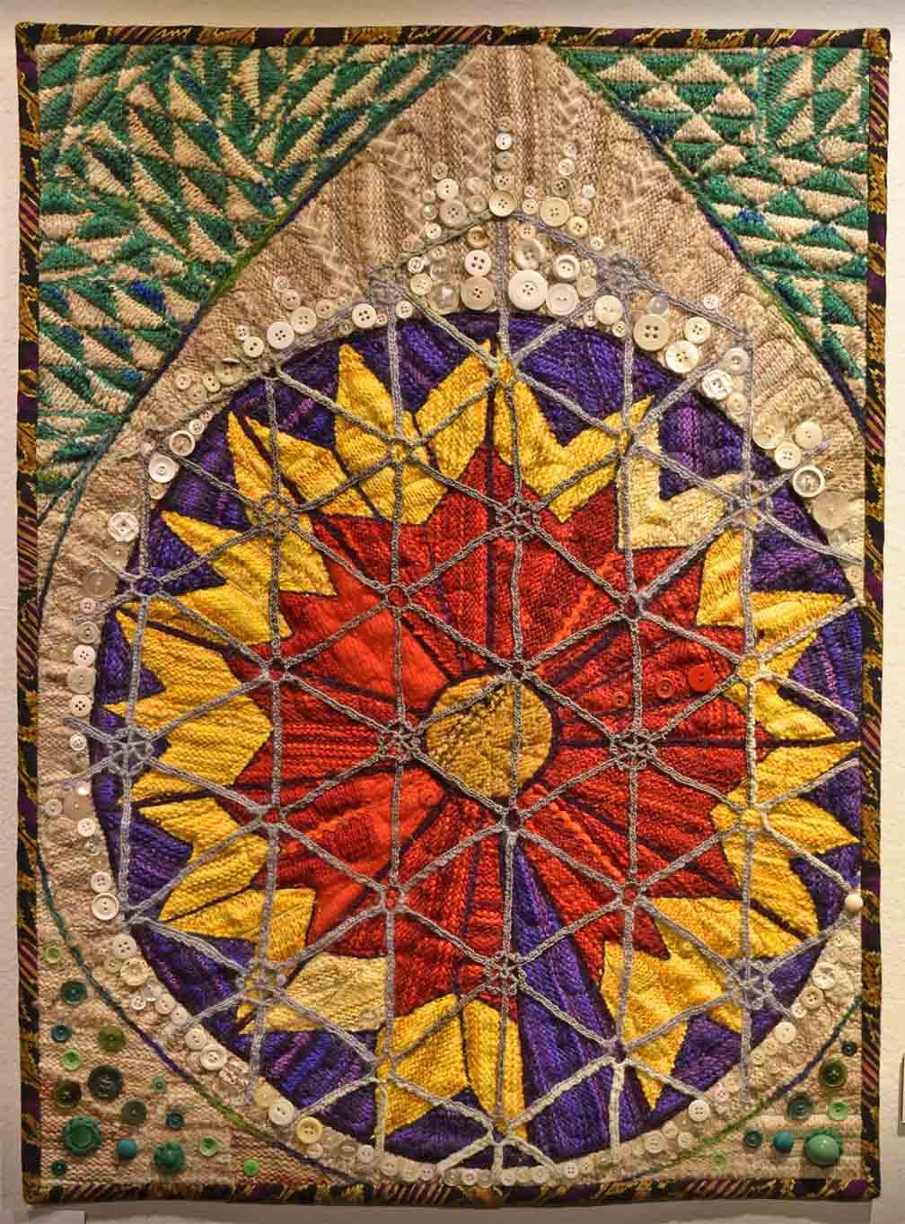 Art quilt in vertical orientation with teardrop shape in which yellow and red floral images are stitched
